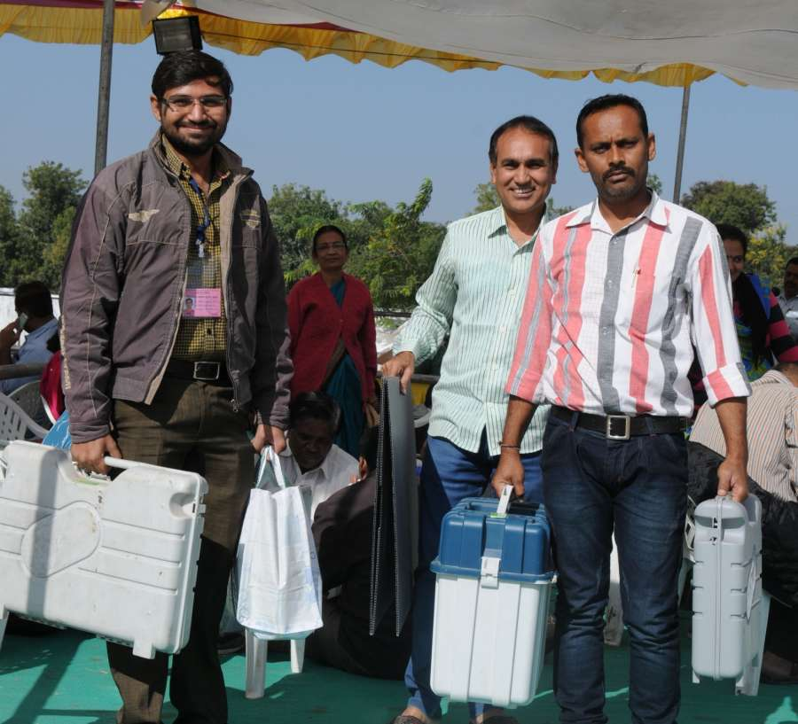 Gandhinagar: Polling officials carry Electronic Voting Machines (EVMs) and other necessary inputs ahead of the second phase of Gujarat Assembly election at a distribution centre in Gandhinagar. (Photo: IANS/PIB)