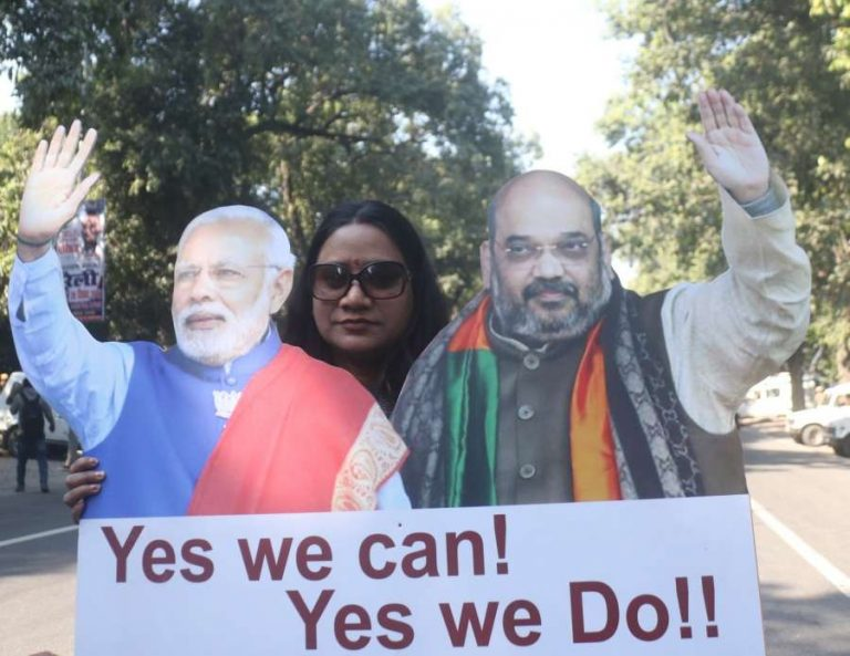 New Delhi: A party worker celebrates with the standies of Prime Minister Narendra Modi and BJP chief Amit Shah as the ruling BJP bagged 104 out of the 182 seats winning the Gujarat assembly elections, at party headquarter in New Delhi on Dec 18, 2017. (Photo: IANS) by .