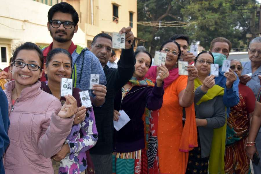 People wait in a queue to cast their vote during Gujarat election.