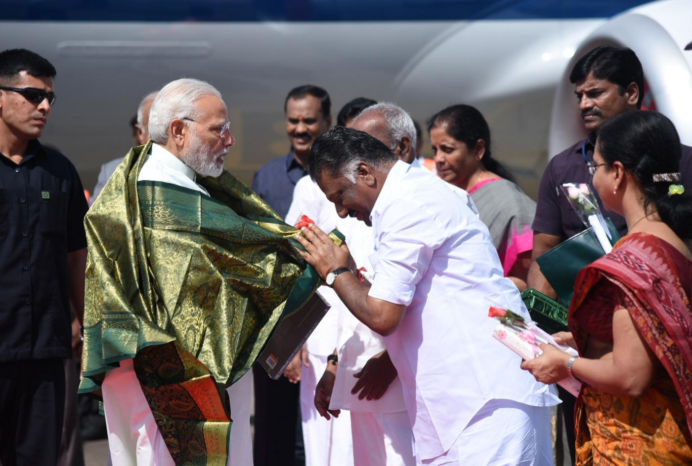 Chennai: Prime Minister Narendra Modi being welcomed by the Deputy Chief Minister of Tamil Nadu O. Panneerselvam, on his arrival, at Chennai, Tamil Nadu on April 12, 2018. (Photo: IANS/PIB) by .