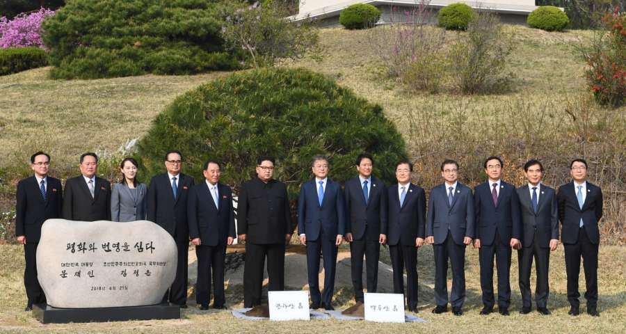 """Panmunjom: South Korean President Moon Jae-in (7th from L), his North Korean counterpart Kim Jong-un (6th from L) and their entourages pose after a tree-planting ceremony to mark their historic talks at the truce village of Panmunjom on April 27, 2018. The phrase on the commemorative stone reads, """"(We) Plant Peace and Prosperity. President Moon Jae-in of the Republic of Korea. Chairman of the State Affairs Commission Kim Jong-un of the Democratic People's Republic of Korea.""""(Yonhap/IANS) by ."""