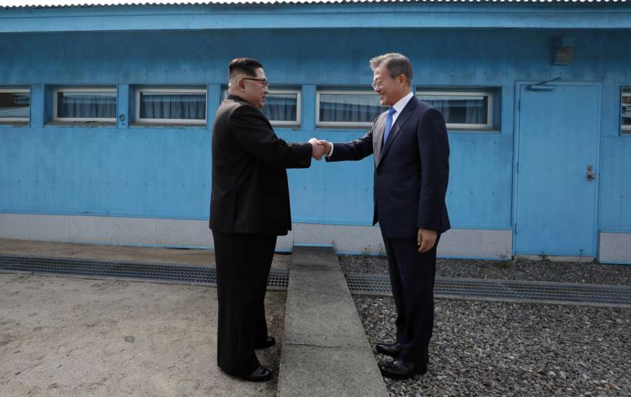 Panmunjom: South Korean President Moon Jae-in (R) and his North Korean counterpart Kim Jong-un shake hands across the military demarcation line prior to Kim's crossing into the South for talks at the Peace House of the truce village of Panmunjom on April 27, 2018. (Yonhap/IANS) by .