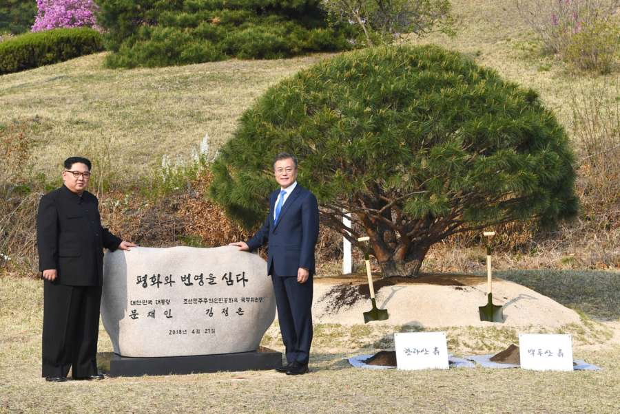 """Panmunjom: South Korean President Moon Jae-in (R) and his North Korean counterpart Kim Jong-un pose beside a commemorative cornerstone after a tree-planting ceremony to mark their historic talks at the truce village of Panmunjom on April 27, 2018, in this photo provided by Yonhap News TV. The phrase on the stone reads, """"(We) Plant Peace and Prosperity. President Moon Jae-in of the Republic of Korea. Chairman of the State Affairs Commission Kim Jong-un of the Democratic People's Republic of Korea."""" (Yonhap/IANS) by ."""