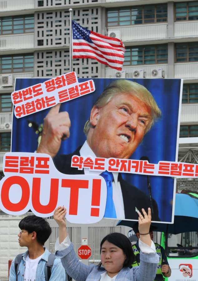 """Seoul: A protester holds a banner that says, """"Trump jeopardizes peace on the Korean Peninsula,"""" during a rally in front of the U.S. Embassy in Seoul on May 25, 2018, to criticize the U.S. government and call for a summit with North Korea as scheduled. On May 24, U.S. President Donald Trump called off his meeting with North Korean leader Kim Jong-un scheduled for June 12, citing the North's """"tremendous anger and open hostility.""""(Yonhap/IANS) by ."""