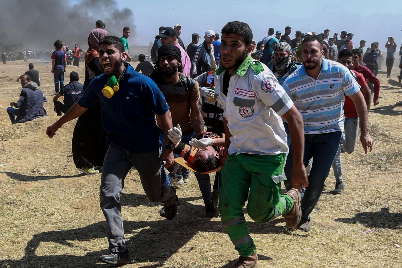 GAZA, May 14, 2018 (Xinhua) -- Palestinian medics and protesters carry an injured man during clashes with Israeli troops near the Gaza-Israel border, east of Gaza City, on May 14, 2018. More than 40 Palestinians, including children, were killed Monday in a day of violent clashes with Israeli forces on Israel's southern border with Gaza, according to the Gaza health ministry. (Xinhua/Wissam Nassar/IANS) by .