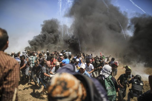 GAZA, May 14, 2018 (Xinhua) -- Palestinian protesters run to take cover from tear gas fired by Israeli troops during clashes, ahead of the Nakba Day, or