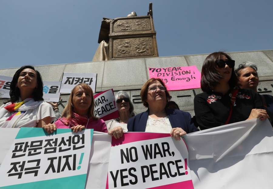 """Seoul: A group of peace activists, including Northern Irish peace activist and Nobel Peace Prize laureate Mairead Maguire (3rd from L), rallies in Seoul on May 25, 2018, to call for the United States to hold a summit with North Korea as scheduled. U.S. President Donald Trump called off his meeting with North Korean leader Kim Jong-un on June 12, citing the North's """"tremendous anger and open hostility."""" (Yonhap/IANS) by ."""