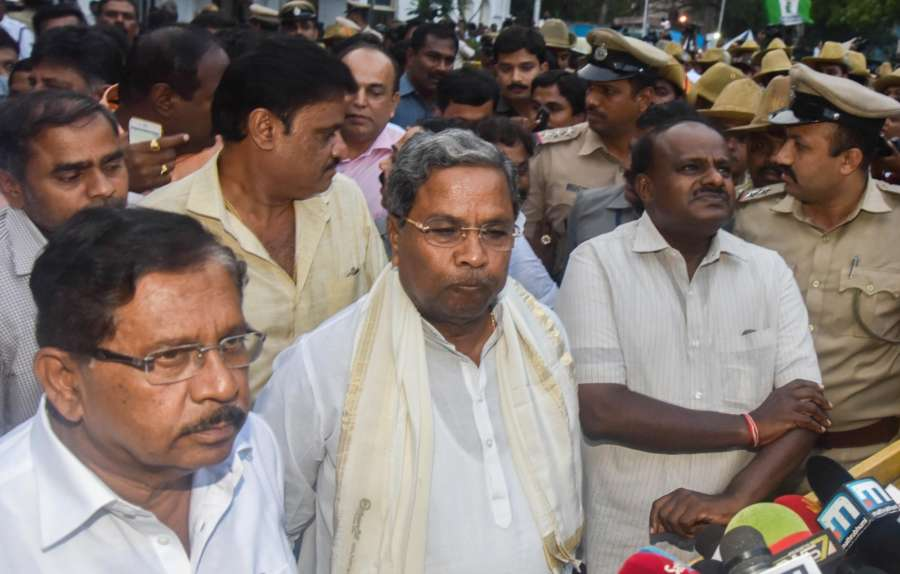 Bengaluru: JD(S) leader H D Kumarswamy with outgoing Karnataka Chief Minister Siddaramaiah and Congress state president G Parameshwara arrive to address the media after meeting Karnataka Governor Vajubhai Vala at Raj Bhavan, in Bengaluru on May 15, 2018. (Photo: IANS) by .