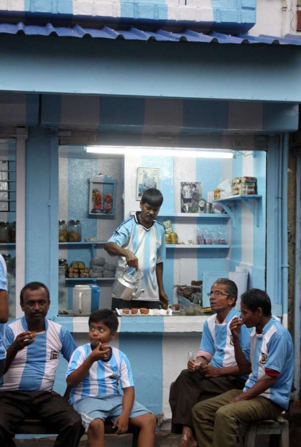 Ichapur: Argentinian fans sip a cup of tea at a tea stall painted in the colours of Argentina flag at Ichapur in West Bengal's North 24 Parganas on June 22, 2018. Expectation, emotion, joy, doubts, uncertainty, surprise, fear, tension and finally disappointment. A lot of disappointment. All that, and in that order, was felt by millions of Argentinians on Thursday as they watched their team beaten 3-0 by Croatia in Russia and almost eliminated from the World Cup. (Photo: IANS) by .