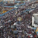 Chennai: People in large numbers participate in the funeral procession of DMK patriarch and former Tamil Nadu Chief Minister M. Karunanidhi, in Chennai on Aug 8, 2018. Karunanidhi was buried beside his mentor C.N. Annadurai on the sands of Marina beach here on Wednesday. After a two-hour funeral procession covering a distance of less than 3 km the tri-colour wrapped body with his trademark black shades and yellow stole still in tact was interred in a freshly dug grave with soldiers giving him a state funeral with full military honours. (Photo: IANS) by .