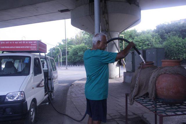 69-year-old Alagarathanam Natarajan refilling the 'matkas' installed by him in Delhi. by .
