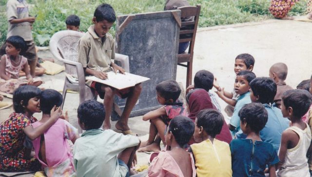 Babar Ali (seated in the chair) teaching ragpickers how to read and write at the age of 9 in the backyard of his home in Murshidabad, West Bengal. by .