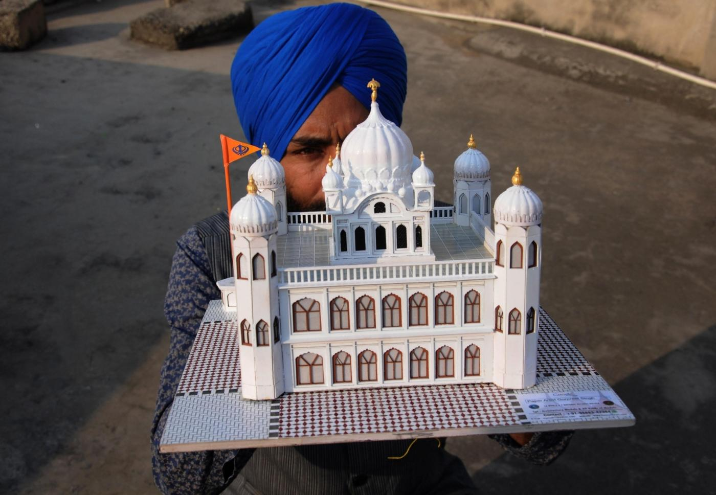 Amritsar: Paper artist Gurpreet Singh shows a model of Kartarpur Sahib, the final resting place of Guru Nank Dev, created by him, on the eve of the first Sikh Guru's birth anniversary, in Amritsar on Nov 22, 2018. (Photo: IANS) by .