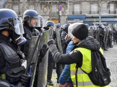 "PARIS, Dec. 8, 2018 (Xinhua) -- A protester confronts police near the Arch of Triumph in Paris, France, on Dec. 8, 2018. Riot police fired tear gas and water cannon at ""Yellow Vests"" protesters marching in Paris on Saturday in the fourth week-end action despite President Emmanuel Macron's series of concessions. (Xinhua/Chen Yichen/IANS) by ."