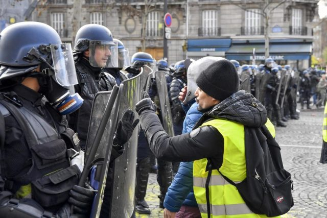 PARIS, Dec. 8, 2018 (Xinhua) -- A protester confronts police near the Arch of Triumph in Paris, France, on Dec. 8, 2018. Riot police fired tear gas and water cannon at