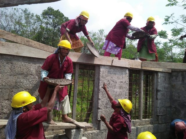 Wearing red shirts over their salwar kameez and a towel around their head, this 20-member all-women group has built their first building all by themselves. by .