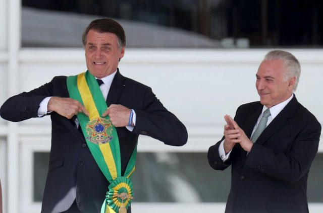 BRASILIA, Jan. 1, 2019 (Xinhua) -- Photo provided by Agencia Estado shows Brazil's new President Jair Bolsonaro (L) pointing at the presidential sash after receiving it from outgoing President Michel Temer (R) in Brasilia, capital of Brazil, on Jan. 1, 2019. Army captain-turned-politician Jair Bolsonaro was sworn in as Brazil's president on Tuesday amid heightened security. (Xinhua/AGENCIA ESTADO/Wilton Junior/IANS) by .
