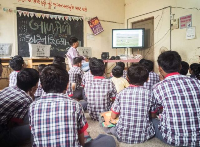 Bhuj (Gujarat): Children learning through the e-learning software in their classroom by .