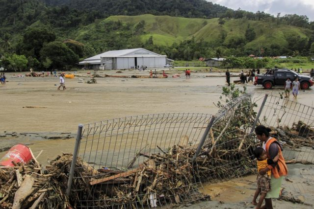 Sentani, March 17, 2019 (Xinhua) A mother holds her child near a collapsed fence after flash floods in Sentani, Indonesia, on March 17, 2019. Sixty-three bodies have been retrieved after flash floods hit Indonesia's easternmost Papua province on Saturday night, and a search and rescue operation is still ongoing for dozens still missing, a rescue team member said on Sunday. (Xinhua/Ikha/IANS) by .