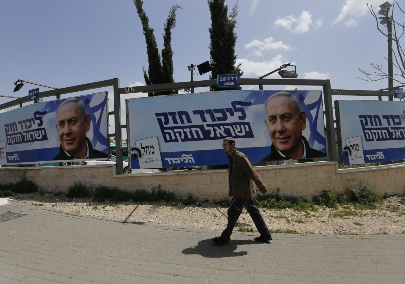 JERUSALEM, April 8, 2019 (Xinhua) -- A man walks past a Likud Party election campaign poster depicting Israeli Prime Minister Benjamin Netanyahu in Jerusalem, on April 7, 2019. (Xinhua/Muammar Awad/IANS) by .