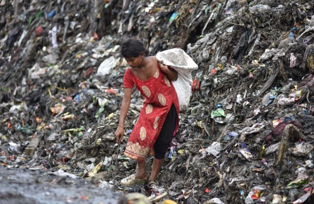 Guwahati : A rag picker seen looking for recyclable items in heaps of garbage at a dump-yard in Guwahati on the eve of World Environment Day, on June 4, 2018. (Photo: IANS) by .