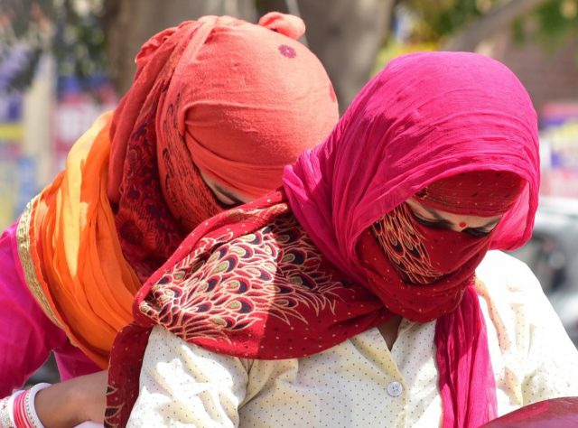 Women cover their faces to avoid scorching sun on a hot day. (File Photo: IANS) by .