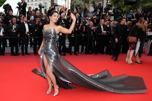 Actress Hina Khan makes an appearance at the red carpet in a metallic grey thigh-high slit sleeveless gown with a long trail on the fifth day of the 72nd Cannes Film Festival on Saturday in Cannes, France. (Photo: Twitter/@isalilsand) by .