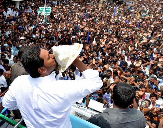Amaravati: YSR Congress Party (YSRCP) chief Jagan Mohan Reddy blows a conch as he celebrates with party workers after the YSRCP emerged victorious in the Andhra Pradesh Assembly elections in Amaravati, on May 23, 2019. He will take oath as the new Chief Minister of Andhra Pradesh on May 30 in the temple town of Tirupati. (Photo: IANS) by .