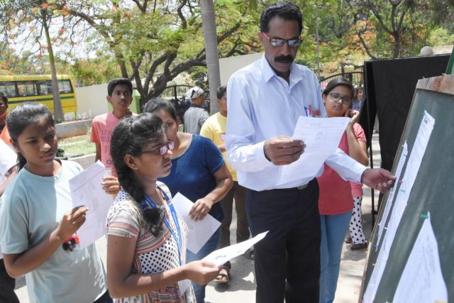 Bengaluru: Applicants check seating arrangement outside their examination center as they arrive to appear for the National Eligibility cum Entrance Test NEET (UG) 2019 in Bengaluru, on May 5, 2019. (Photo: IANS) by .
