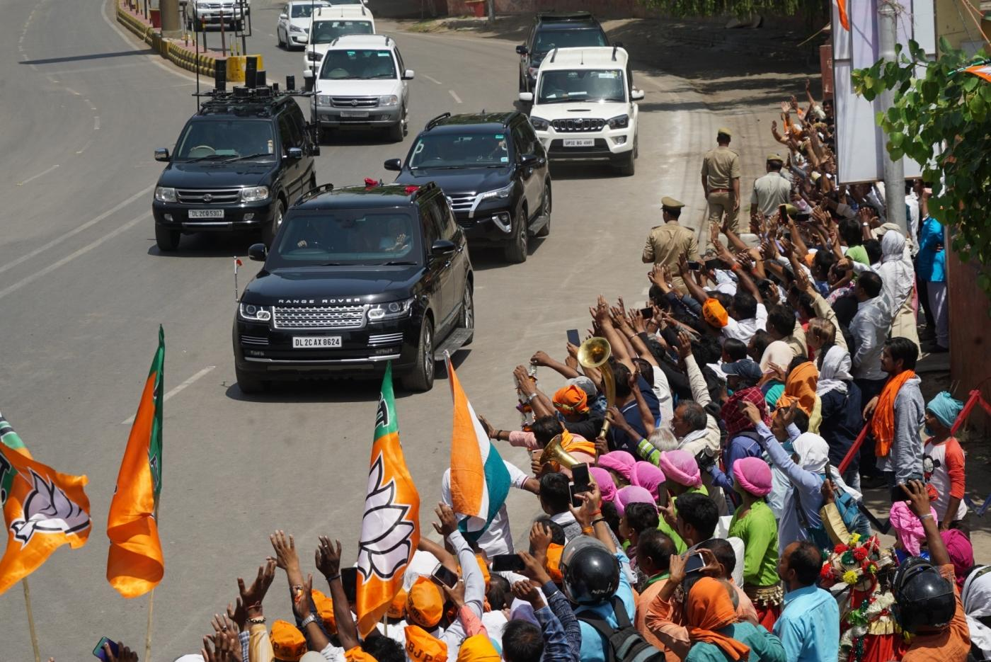 Varanasi: People queue up to wave out to Prime Minister Narendra Modi as he heads to the Kashi Vishwanath Temple in Varanasi on May 27, 2019. (Photo: IANS) by .