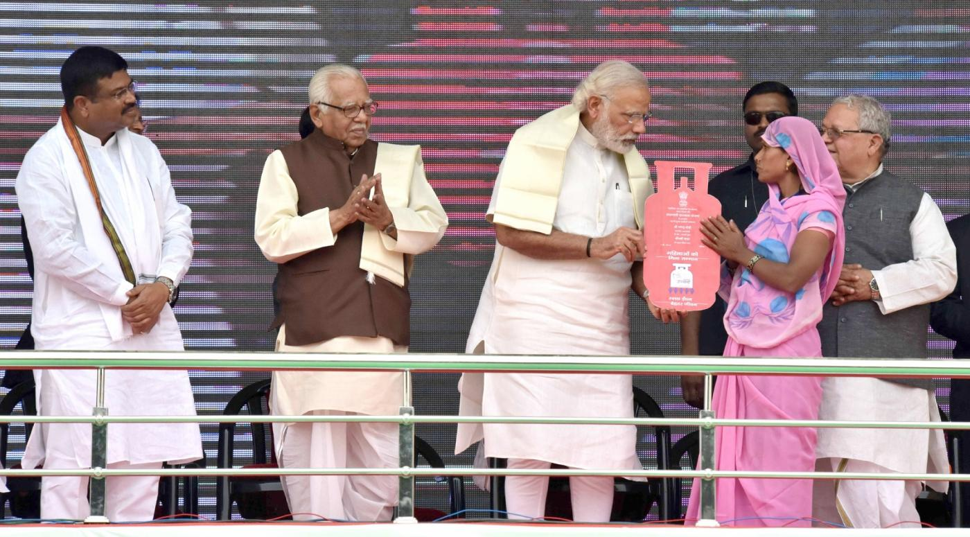 Ballia: Prime Minister Narendra Modi distributes free LPG connections to the beneficiaries, under Pradhan Mantri Ujjwala Yojana, in Ballia of Uttar Pradesh on May 1, 2016. Also seen Uttar Pradesh Chief Minister Ram Naik Union Petroleum Minister Dharmendra Pradhan and Union MSME Minister Kalraj Mishra. (Photo: IANS/PIB) by .