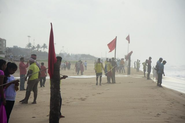 Puri: Red flags and ropes being placed at the banks of the Puri beach as precautionary measures to keep tourists away from the beach in the wake of severe cyclonic storm 'Fani' in Odisha's Puri on May 2, 2019. The cyclonic storm is likely to hit Odisha coast between Gopalpur and Chandbali on May 3 evening. According to the India Meteorological Department, cyclone Fani, which has turned into an
