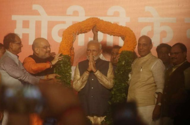 New Delhi: Prime Minister Narendra Modi being welcomed by BJP chief Amit Shah, party leader Shivraj Singh Chouhan and Union Ministers Rajnath Singh and J.P. Nadda, on his arrival to address party workers at the party's headquarters in New Delhi, on May 23, 2019. In a stunning electoral showing, the BJP led by Prime Minister Narendra Modi was on Thursday set to retain power for another five years after making a sweep of the Lok Sabha battle and mauling the opposition. (Photo: Bidesh Manna/IANS) by .