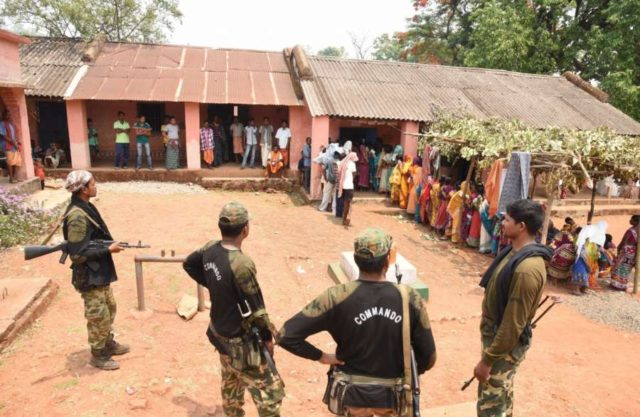 Kandhamal: Security personnel stand guard as people vote for the second phase of 2019 Lok Sabha elections, at a polling booth at Sadingia in Odisha's Kandhamal, on April 18, 2019. (Photo: IANS) by .