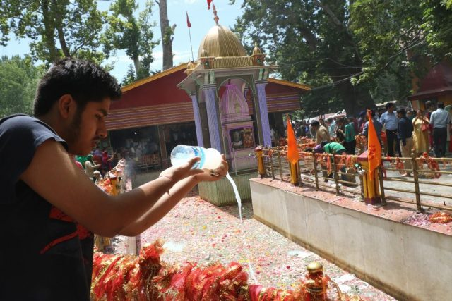 Srinagar: A devotee performs rituals during Kheer Bhawani Mela at Mata Kheer Bhawani Shrine in Jammu and Kashmir's Ganderbal district on June 20, 2018. Kashmiri Pandits started arriving here on Wednesday to pray for peace and prosperity at the shrine that is is dedicated to Hindu deity Mata Ragnya, who according to Hindu beliefs came to Kashmir from Sri Lanka during the rule of Ravana and is considered to be the holiest Kashmiri Pandit shrine in Kashmir Valley. (Photo: IANS) by .