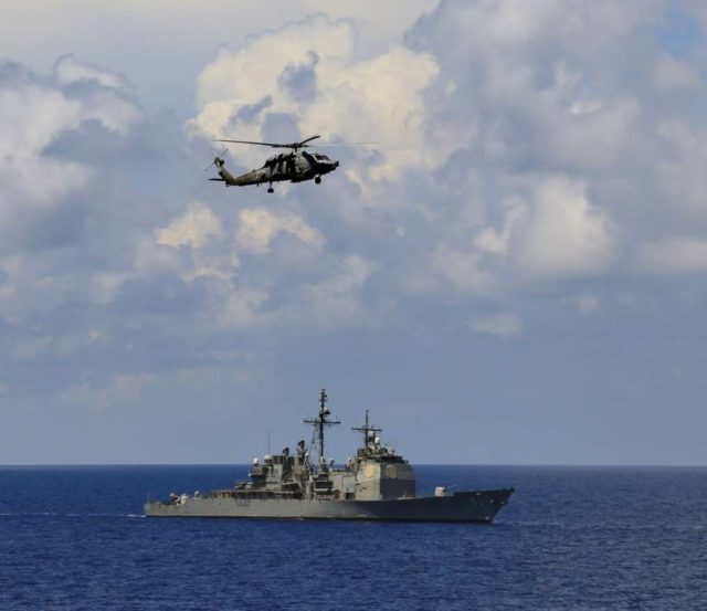 Indian Ocean: Sikorsky Multi-role helicopter and USS Normandy, a Ticonderoga class destroyer during the ongoing Exercise Malabar-2015 in the Indian Ocean on Oct 18, 2015. (Photo: IANS) by .
