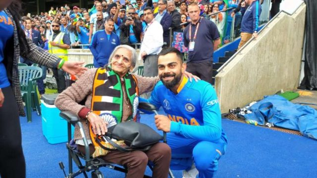 "Birmingham: India skipper Virat Kohli greets 87-year-old Charulata Patel, who became a social media sensation after an image of her blowing a horn to cheer the Men in Blue during their World Cup match against Bangladesh went viral, at the Edgbaston Cricket Ground on July 2, 2019. ""I have been watching cricket for last many decades. Earlier, I used to watch on TV when I was working, but now that I am retired I watch it live,"