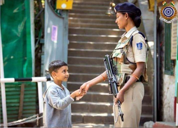Woman CRPF personal shaking hands with kid in Kashmir. by .