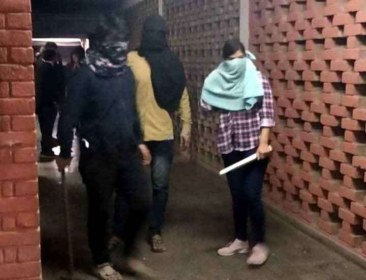 New Delhi: Students roam around the JNU hostel with rods and sticks after clashes erupted between groups of students at JNU campus in New Delhi on Jan 5, 2020. (Photo: IANS) by .