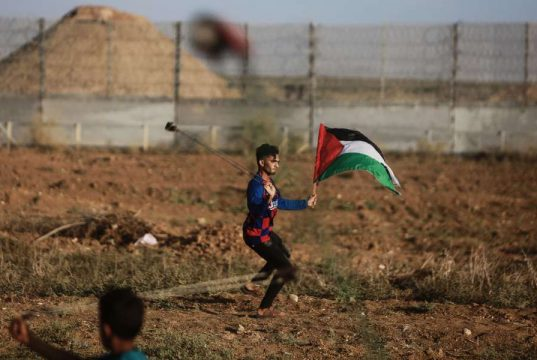 GAZA, Oct. 11, 2019 (Xinhua) -- A Palestinian protester uses a slingshot to throw a stone at Israeli troops during clashes on the Gaza-Israel border, east of Gaza City, on Oct. 11, 2019. At least 49 Palestinians were injured on Friday afternoon during clashes between hundreds of Palestinian demonstrators and Israeli soldiers in the eastern Gaza Strip close to the border with Israel, a local official said. (Photo by Mohammed Dahman/Xinhua/IANS) by .
