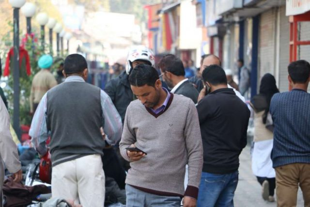Srinagar: People busy on their mobile phones as services of all post paid mobile phones were resumed across the Kashmir Valley after it was suspended on the intervening night of August 4 and August 5 ahead of the scrapping of Article 370; in Srinagar on Oct 14, 2019. (Photo: IANS) by .