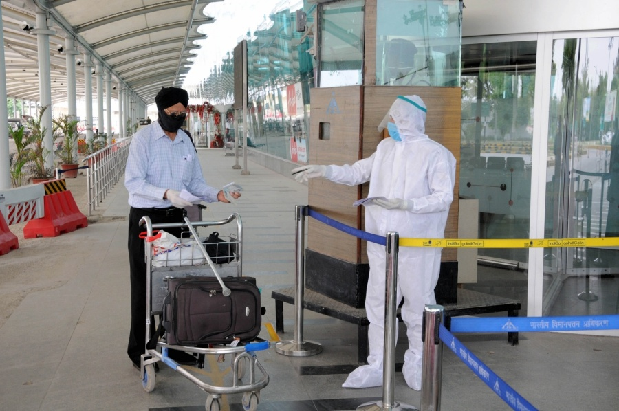 Amritsar: A security personnel wearing Personel Protective Equipment (PPE) suit checks the passports of British nationals before check-in for a special flight to London during the extended nationwide lockdown imposed to mitigate the spread of coronavirus; at the Sri Guru Ram Dass Jee International Airport in Amritsar on Apr 25, 2020. (Photo: IANS) by .